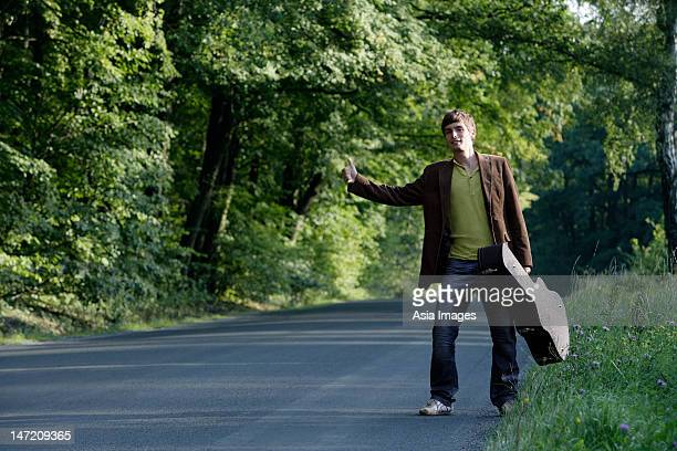 Young hitchhiking man with guitar