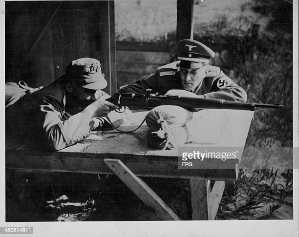 Young Hitler Youth recruit, being trained in rifle use by a soldier during World War Two, Germany, circa 1939-1945.