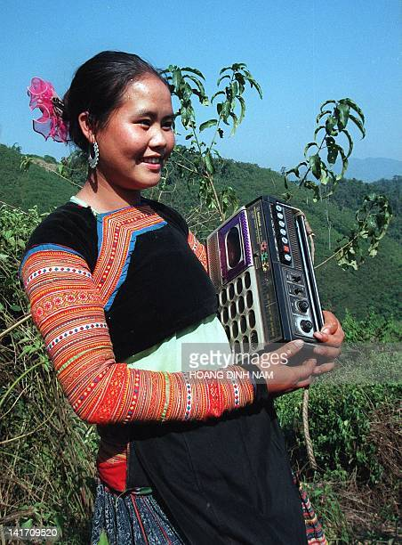 A young H'Mong hill tribe girl enjoys listening to music from a radiocassette player she carries along with her during an outing with friends 23...
