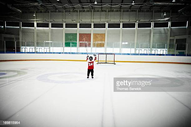 young hockey player arms raised after scoring - celebration photos stock pictures, royalty-free photos & images