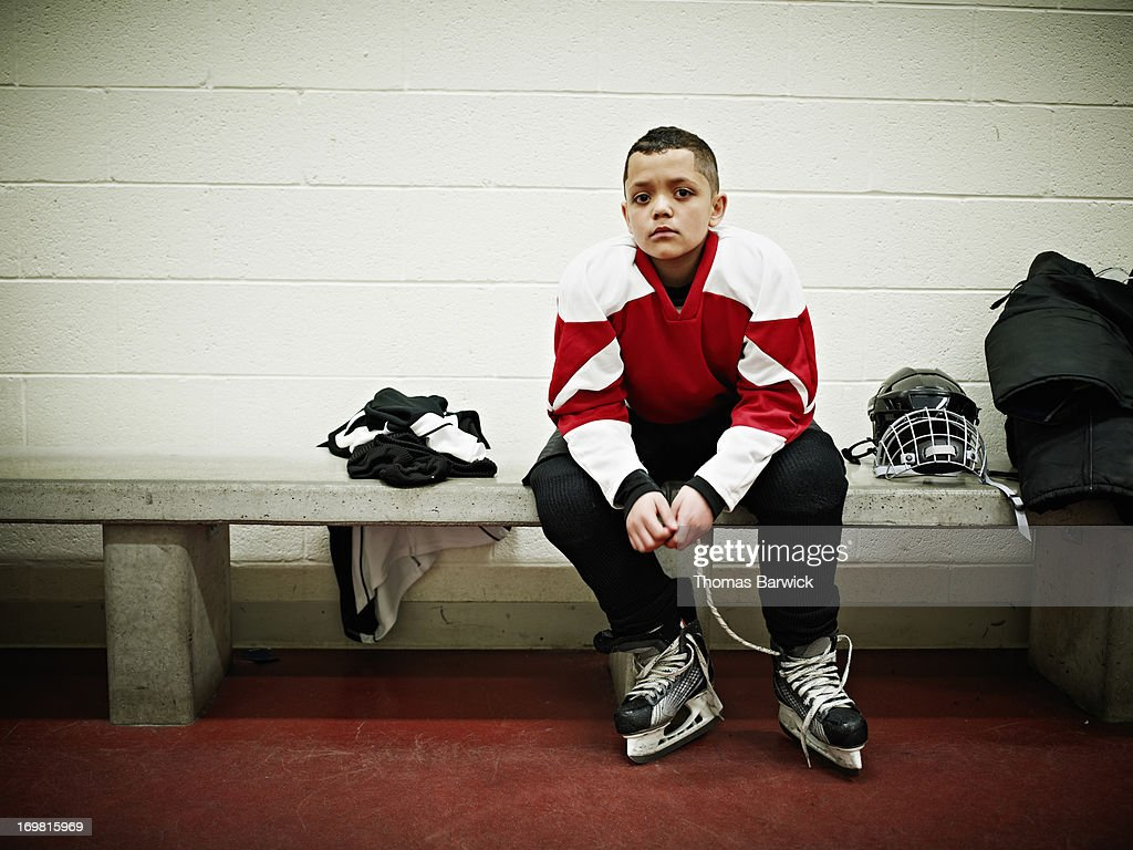 Young hockey player in locker room before game : Stock Photo