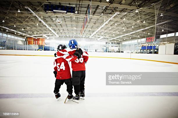 Young hockey players standing on ice rear view