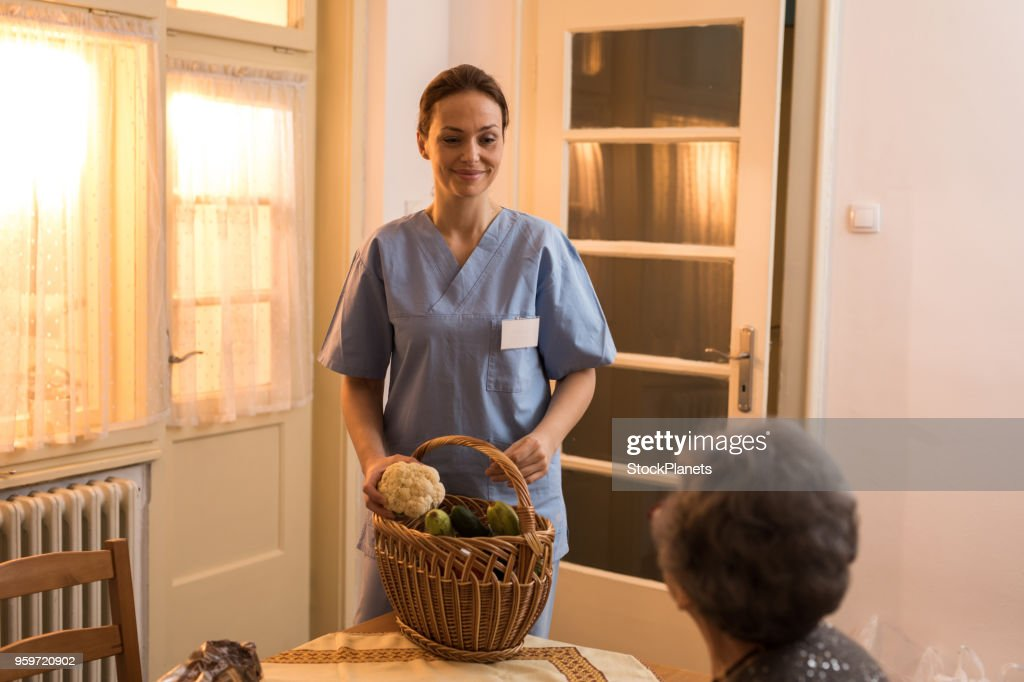 Young home caregiver nurse delivered food to senior womens home : Stock Photo