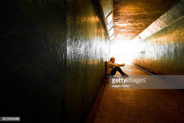 young homeless adult male sitting and begging in subway tunnel - addict stock photos and pictures