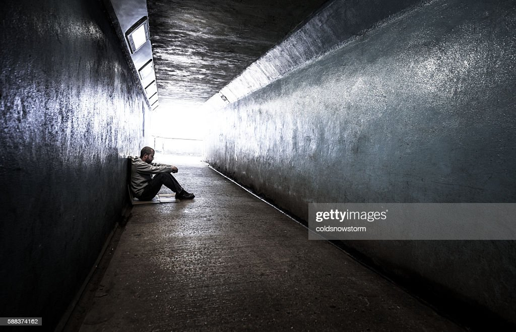 Young homeless adult male sitting in subway tunnel : Stock Photo