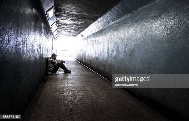 young homeless adult male sitting in subway tunnel - defeat stock photos and pictures