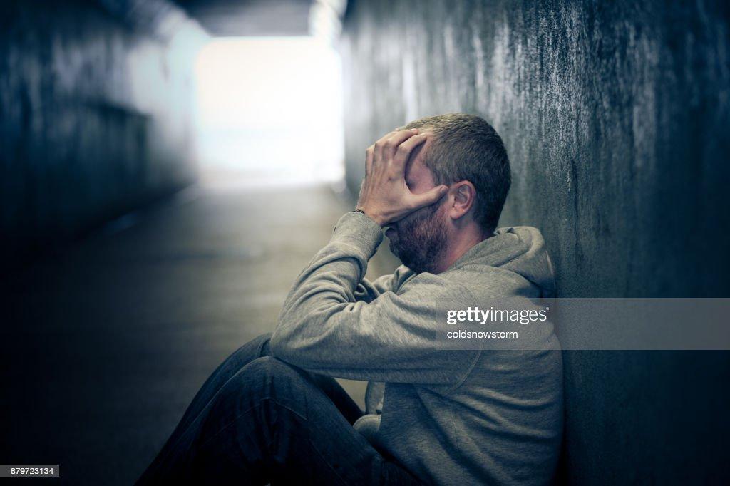 Junge Obdachlose Kaukasischen Männchen sitzen in dunkle u-Bahn-Tunnel : Stock-Foto