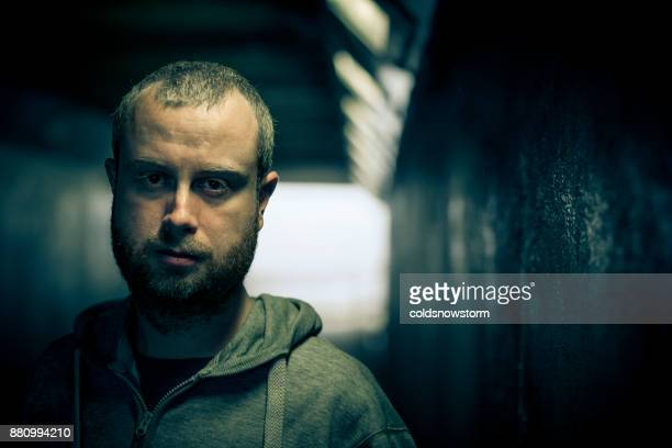 Young homeless caucasian male standing and looking at camera in dark subway tunnel