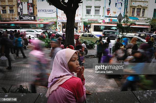 Young homeless girl is standing in the middle of the busy street during the peak weekend at the Jalan Tunku Abdul Rahman, Kuala Lumpur, Malaysia.