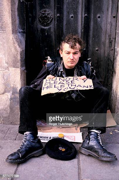 Young homeless man begging outside of Sainsburys supermarket in Camden London