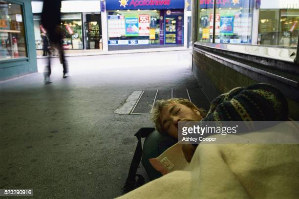 young homeless man sleeping on sidewalk in leeds - homelessness stock pictures, royalty-free photos & images