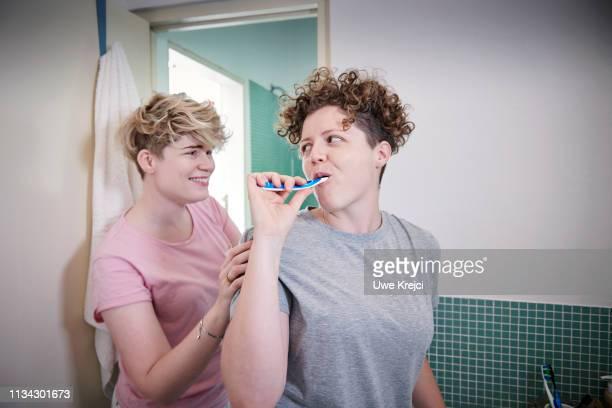 Young homosexual couple in bathroom, brushing teeth