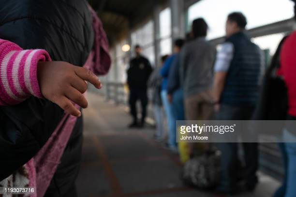 A young Honduran asylum seeker waits with her family on the international bridge from Mexico to the United States on December 09 2019 next to the...