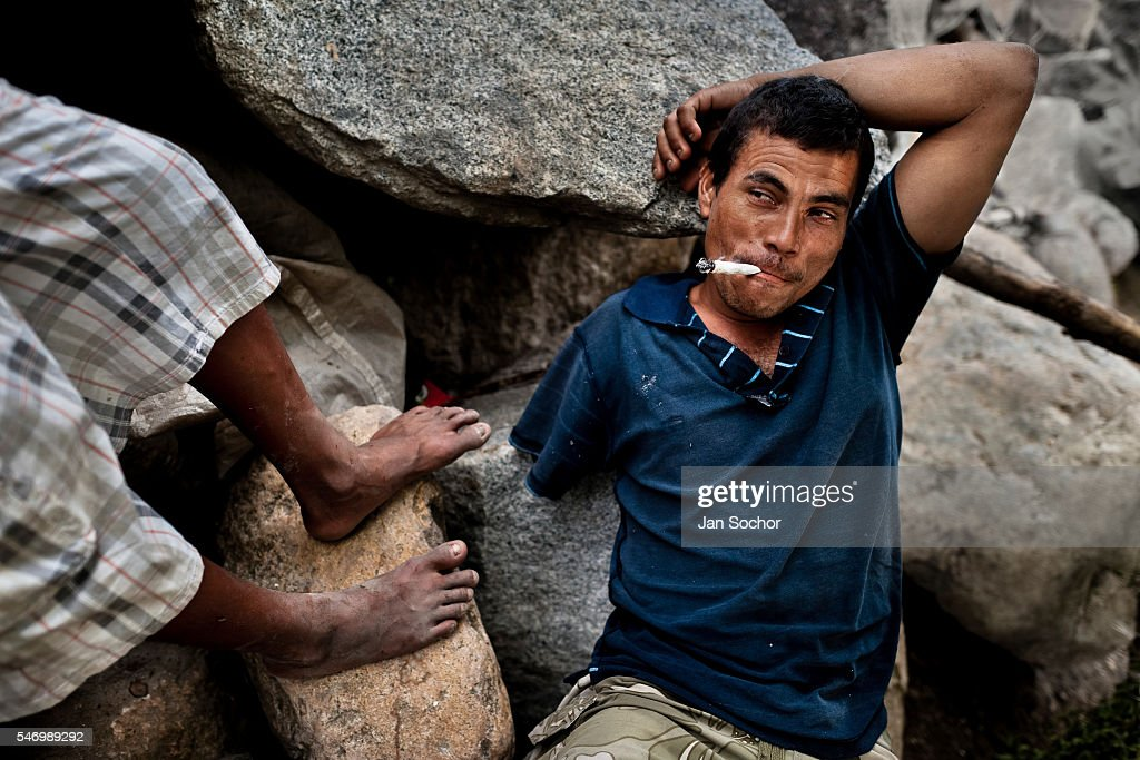 A young Honduran immigrant, having his arm amputated by a train during his previous attempt to get illegally to the United States, smokes marijuana on the bank of Suchiate river on the Guatemala-Mexico border, on 23 May 2011. Between 2010 and 2015, the US and Mexico have apprehended almost 1 million illegal immigrants from El Salvador, Honduras, and Guatemala. While the economic reasons remain the most frequent motivation for people from Central America to illegally immigrate to the US, thousands of Salvadorans, Guatemalans, and Hondurans, many of them minors, seek asylum in the US due to the thriving crime and gang-related violence in their region (known as the Northern Triangle). Taking an exhausting and risky journey, riding thousands of miles atop the cargo trains, facing a physical danger and extortion from the organized crime groups that control migrant routes, the undocumented still flee to the US, looking for their American dream.
