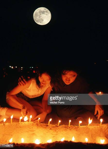 A young Hong Kong couple burn candles and enjoy the annual Moon Festival on a local beach Residents of Hong Kong flock to beaches and parks during...