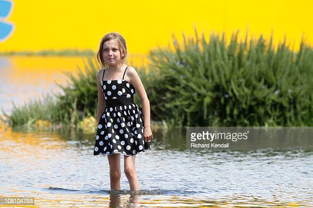 A young Horsham girl walks down a flooded town street as waters begin to drop on January 18 2011 in Horsham Australia Residents and emergency crews...