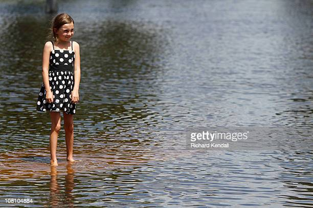 A young Horsham girl walks down a flooded town street on January 18 2011 in Horsham Australia Residents and emergency crews sandbagged properties and...