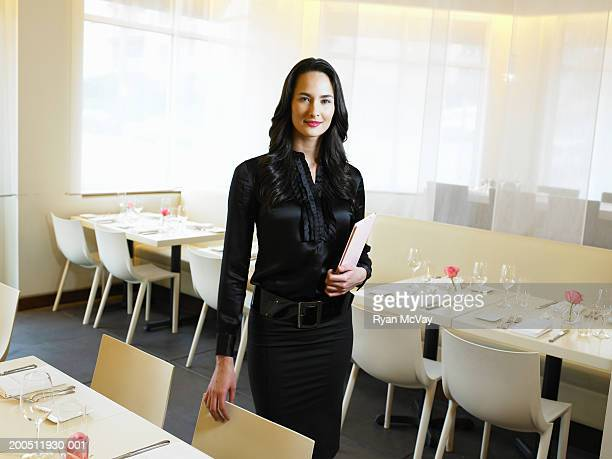 Young hostess holding menus in restaurant, portrait