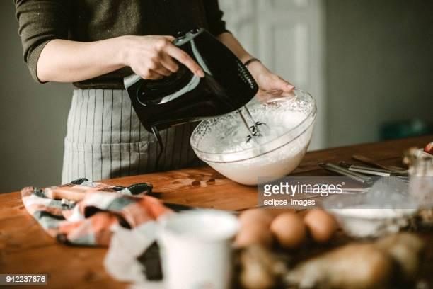 young hous wife mixing wiped cream - montare foto e immagini stock
