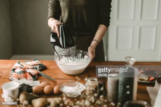 junge haus frau mischen wischte creme - küchenbedarf stock-fotos und bilder