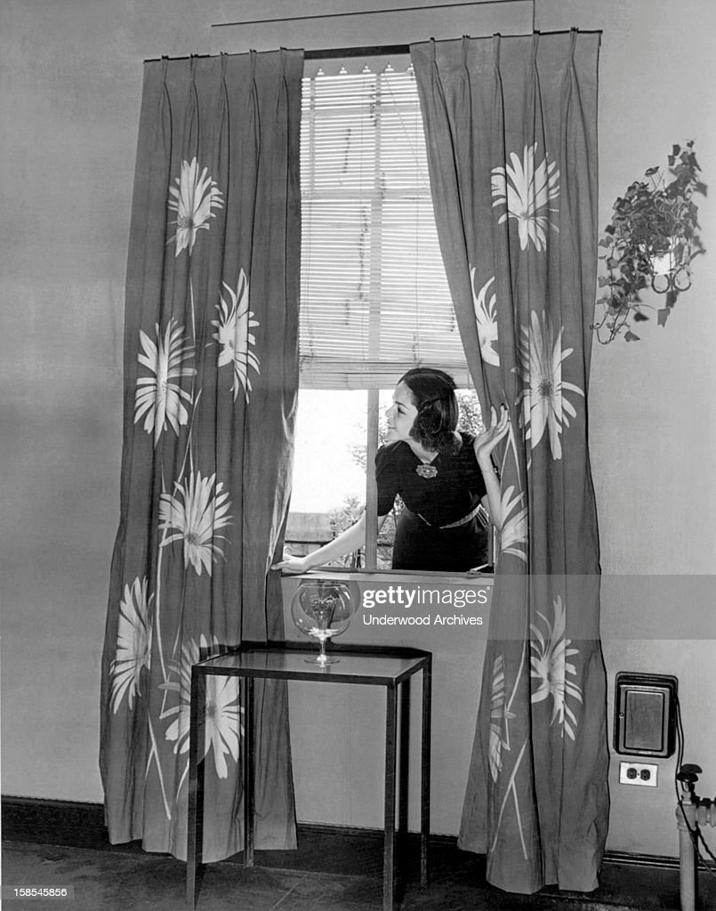 A young housewife leans in through the window to check out the curtains she has just made and hung in her living room, August 2, 1938.