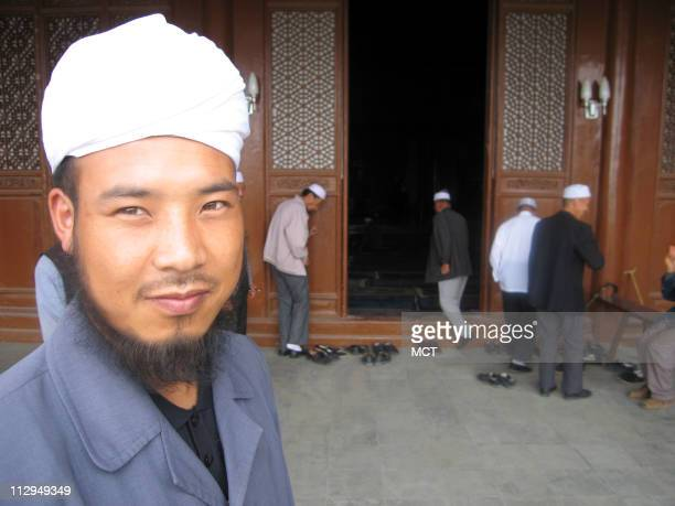 A young Hui minority student of Islam prepares to enter a mosque in the city of Tongxin China The Hui ethnic minority is descended from Silk Road...