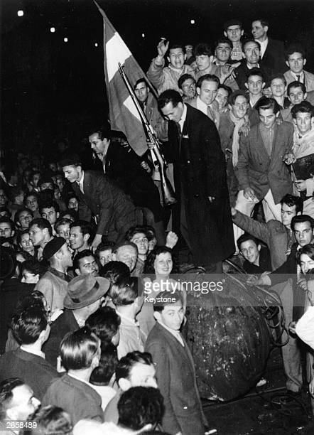 Young Hungarians holding a Hungarian flag standing on a fallen statue at Budapest during the Uprising