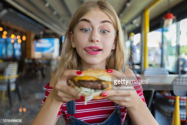 young hungry woman - hamburger stock pictures, royalty-free photos & images