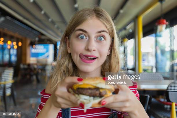 young hungry woman - fast food restaurant stock pictures, royalty-free photos & images