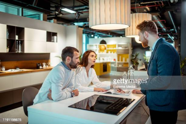 young husband and wife getting informed about a kitchen appliance from a brochure with assistance from a store employee - kitchenware shop stock pictures, royalty-free photos & images