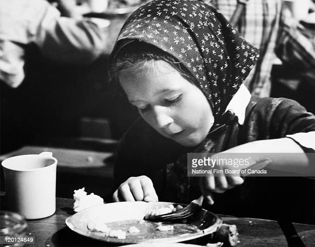 Young Hutterite girl eating at the dinner table Northeast Alberta Canada 1963 Photo taken during the National Film Board of Canada's production of...