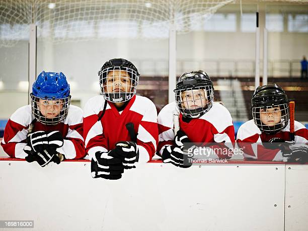 young ice hockey players in players box - ice hockey stock pictures, royalty-free photos & images