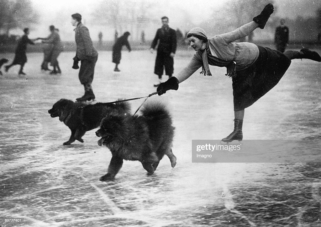 A young ice-scater with her dogs is sliding on the ice. Photograph. Around 1935.