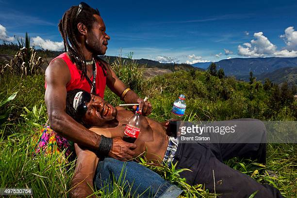 Young illegal gold miners lie drunk and singing on their remaining local land overlooking the dump sites of the Porgera Joint Venture Mine Papua New...