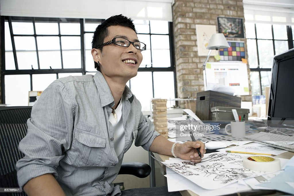 Young illustrator smiling away from the camera : Stock Photo