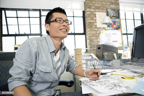 young illustrator smiling away from the camera - illustrator stock photos and pictures