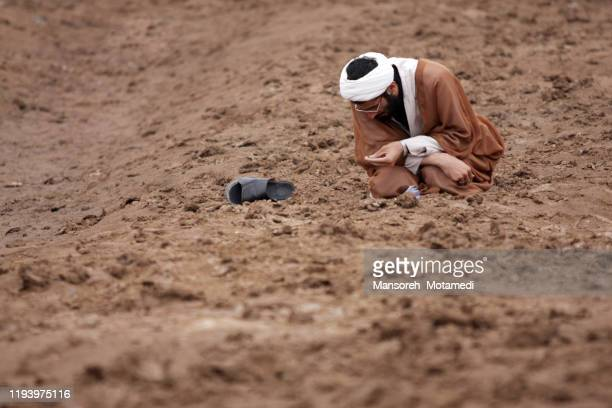 young imam praying outdoors - war and conflict stock pictures, royalty-free photos & images