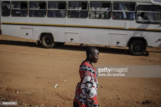 A young imbali covered with fabric bearing portraits of Swaziland KIng Mswati III walks past a bus in which maidens are getting ready on the last day...