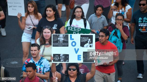 TOPSHOT Young immigrants activists and supporters of the DACA program march through downtown Los Angeles California on September 5 2017 after the...