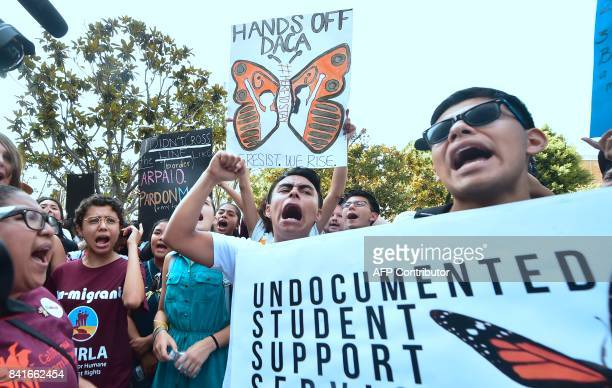 Young immigrants and supporters walk holding signs during a rally in support of Deferred Action for Childhood Arrivals in Los Angeles California on...