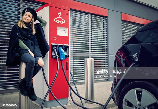 Young impatient girl is charging her electric car at the charging station