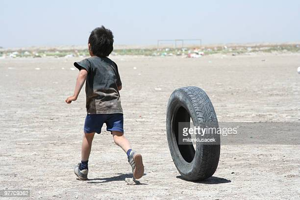 Young impoverished boy playing with a car tire on dirt patch