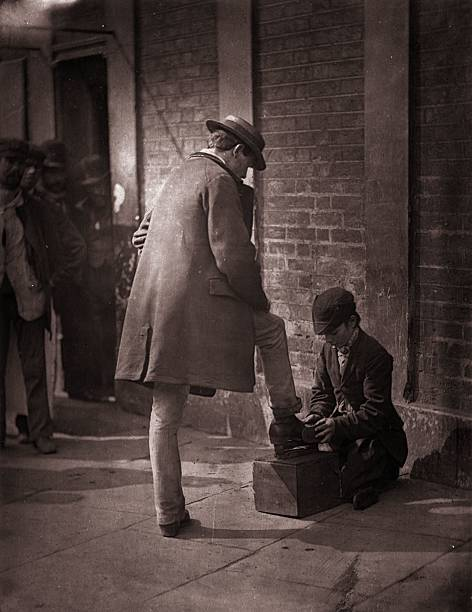 A young independent shoeblack shines the boots of a...