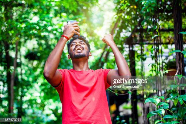 young indian asian man screaming for a celebration while looking at smart phone - omar shamsuddin stock pictures, royalty-free photos & images