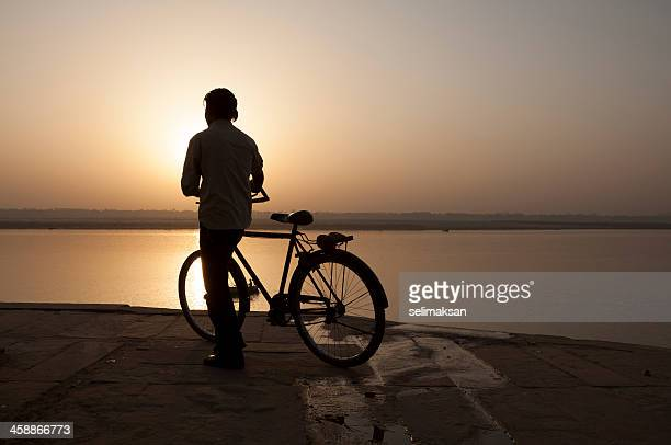 Young Indian biker watching sunset over Ganges River in Varanasi