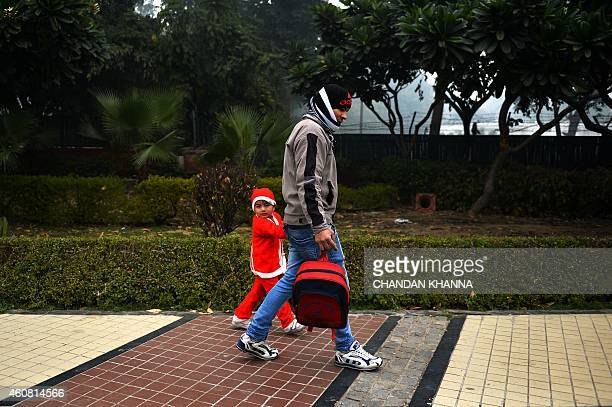 A young Indian boy dressed as Santa Claus is accompanied to school a day ahead of Christmas in New Delhi on December 24 2014 Despite Christians...