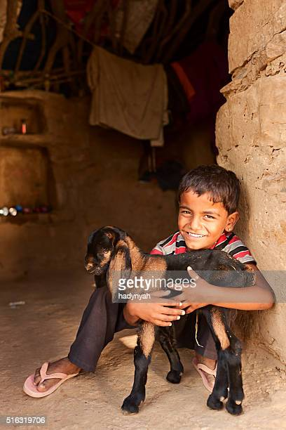 Young Indian boy holding a goat in village on desert
