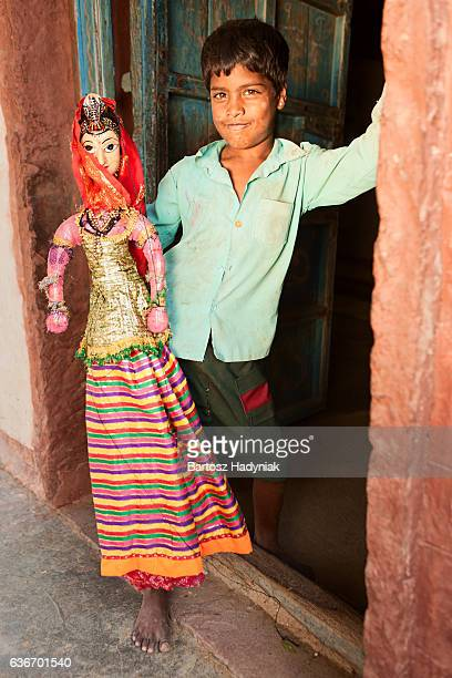 Young Indian boy holding puppet, Rajasthan, India.