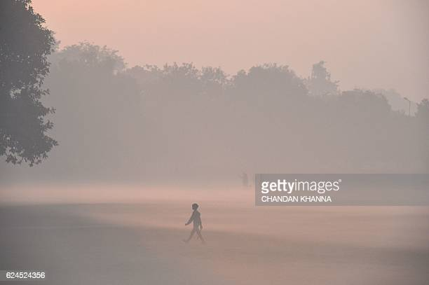 TOPSHOT A young Indian boy walks on a foggy field in New Delhi on November 20 2016 / AFP / CHANDAN KHANNA