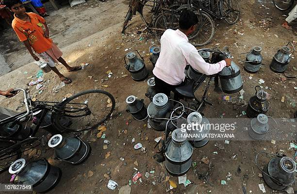 A young Indian boy watches as a milkman load milk onto his bicycle outside a railway station in New Delhi on September 24 2009 A large portion of the...